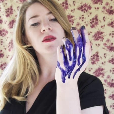 Woman Holding Purple Shampoo On Hand